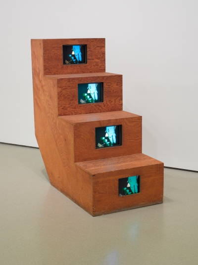 Four monitors incased in plywood. They all show the same footage of a figure standing in a dark space.
