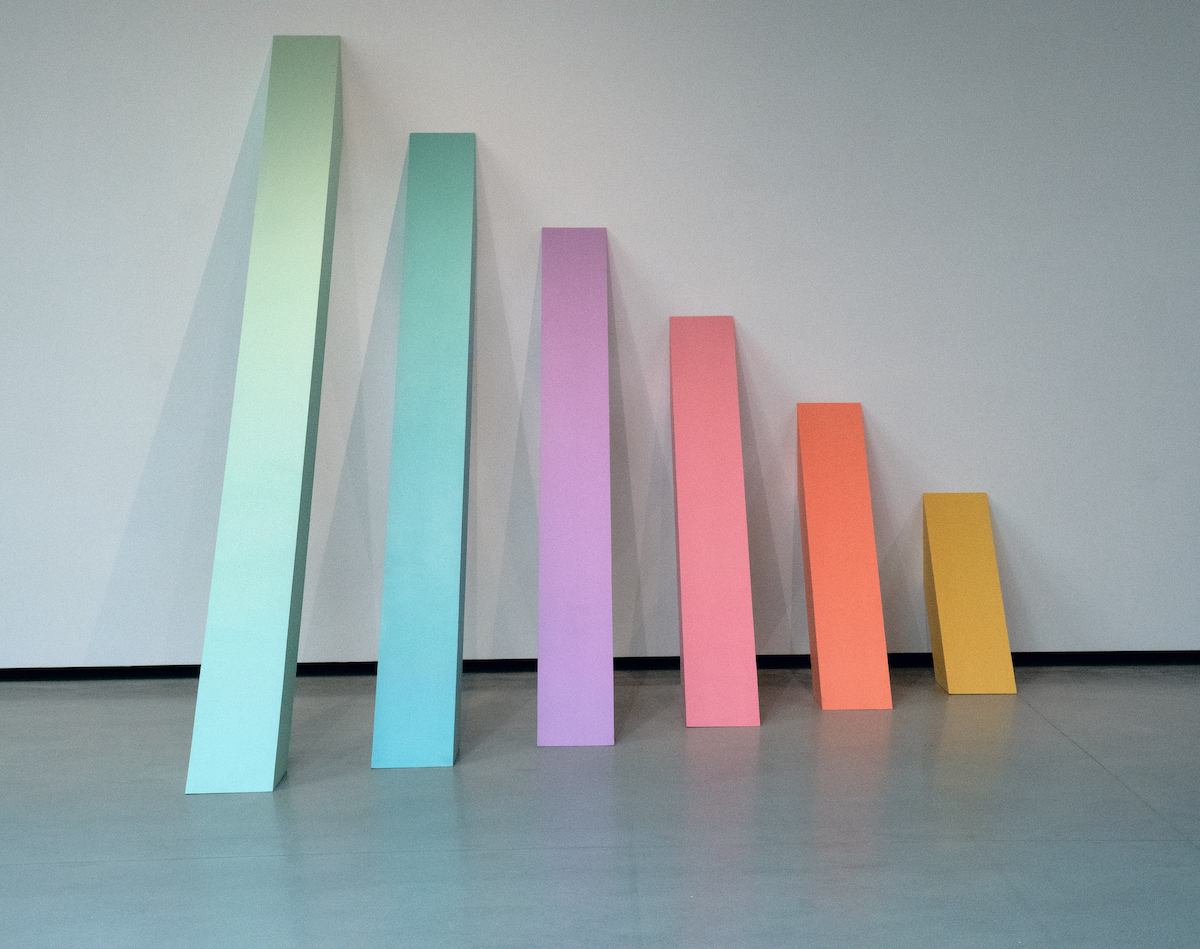 A series of plywood rectangles leaned against a wall. They are colored and descend in size as they move from left to right.