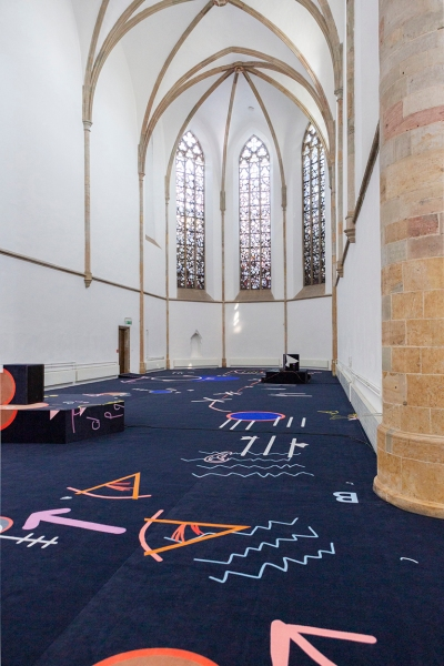 View of a church nave with high vaults. On the floor, there's a navy blue carpet with colorful symbols like arrows and zig zags.