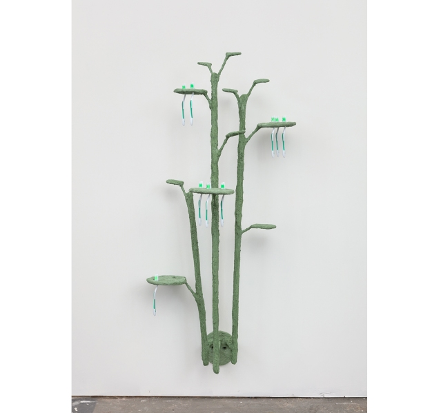 Four green branches with leaves are mounted to a wall, holding a dozen or so green toothbrushes.