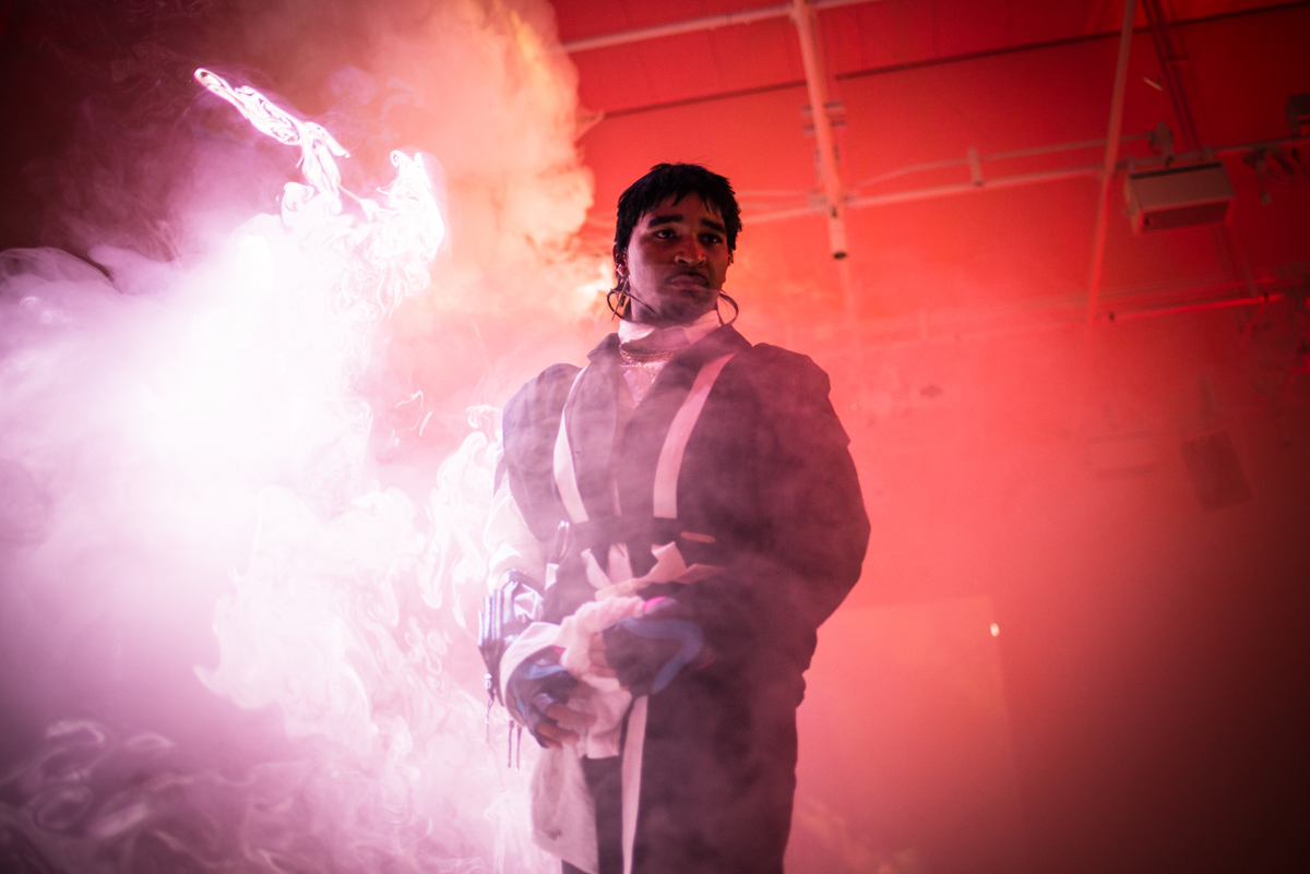 A Black man in a black-and-white overcoat walks among fog and orange-pink lights.