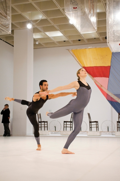 A male dancers holds onto a female dancer. They perform in a gallery in front of works by Marcel Duchamp and others.