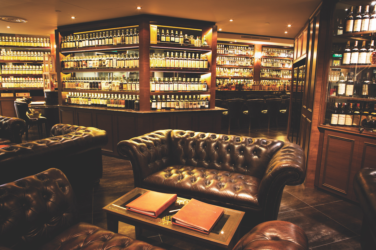 A sensually lit club with a leather couch and bottles of whiskey lining a wall.