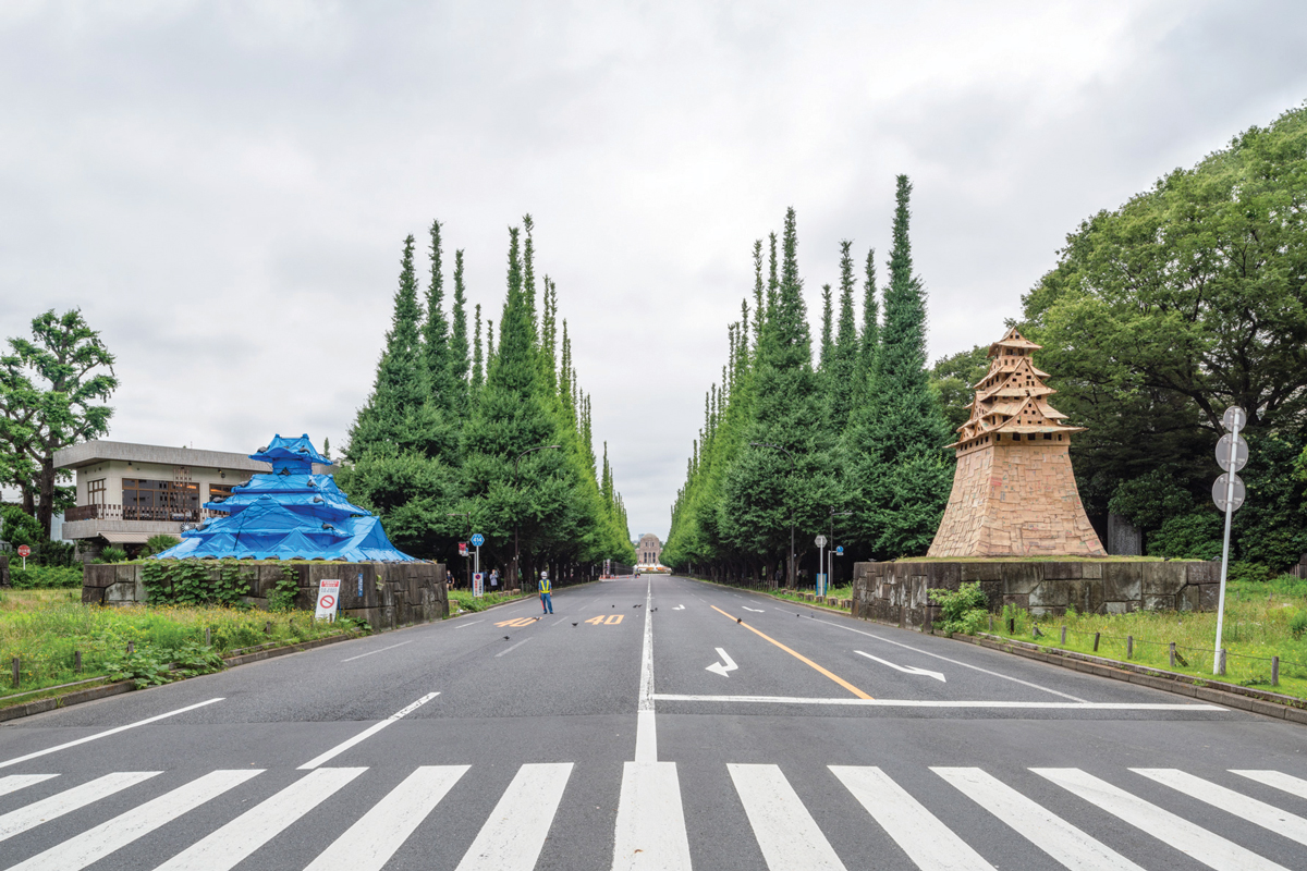 View of Tokyo street with a blue tarp castle-like structure installed opposite a taller one in wood.