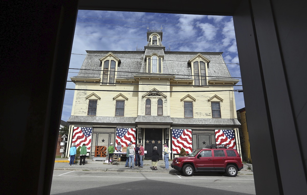 An old three-story building with American flags lining its front. Parked in front of it is a red car.