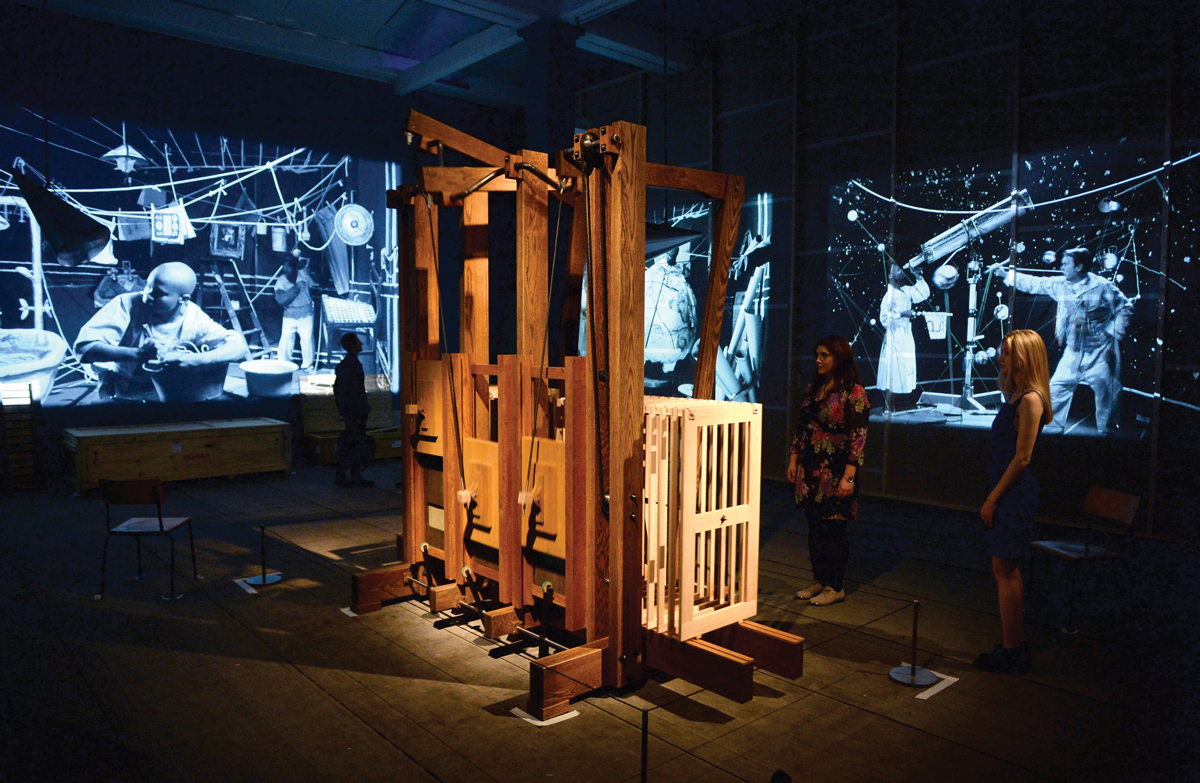 A multimedia video installation with two screens in the background and a wooden structure in the foreground.