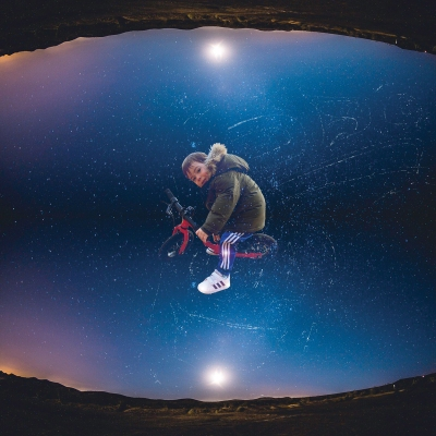 A photo of Nicholas Galanin's son on a tricycle superimposed over a night celestial sky.