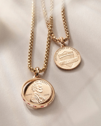 Two necklaces holding pennies draped over a beige background.