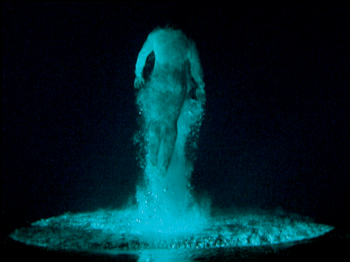 Video still of a man diving into water that has been reversed. The image is mostly black and teal.
