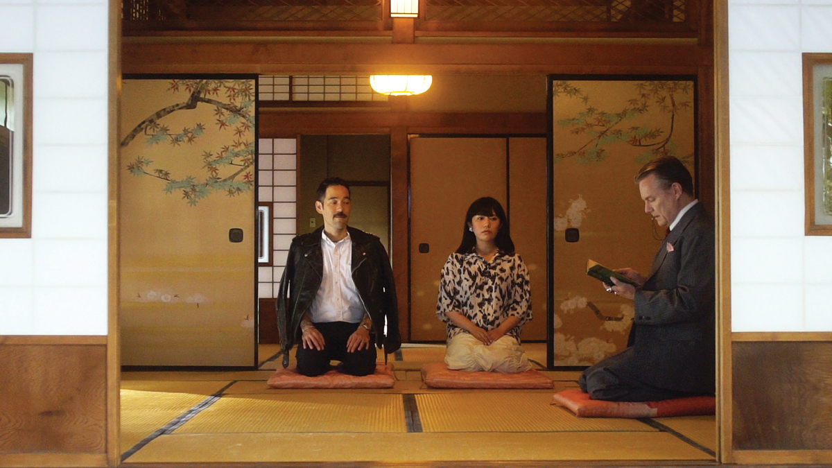 A man and a woman sit in seiza position in a traditional Japanese interior. They look forward at the camera. At right, a man with a book reads from it.