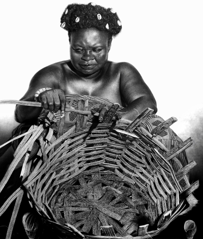 A hyperrealistic black-and-white drawing of an Igbo woman in traditional dress with seashells in her hair at work weaving a basket.