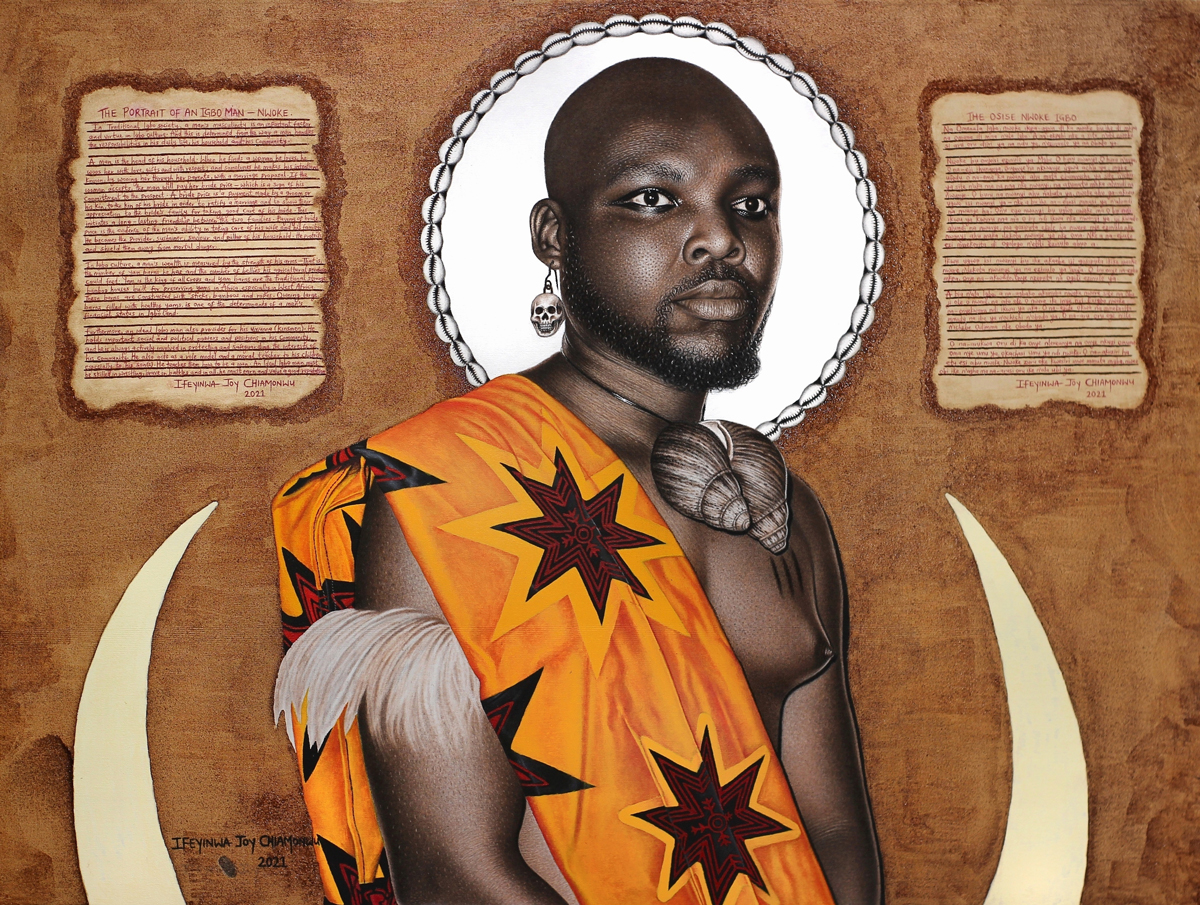 A hyperrealistic drawing of an Igbo man wearing an orange traditional garment, a necklace of seashells, an upper arm piece of feathers. His head is surrounded by a white halo. On either side is a description in English (left) and Igbo (write) about Igbo men.