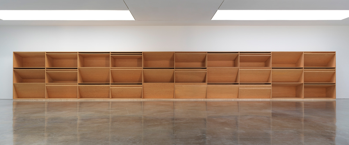 Installation view of a plywood work by Donald Judd. It is 80 feet wide and divided into 10 vertical sections with various unique gaps and spaces in between.