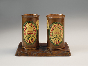 Two beer cans cast in bronze with the label designs painted over