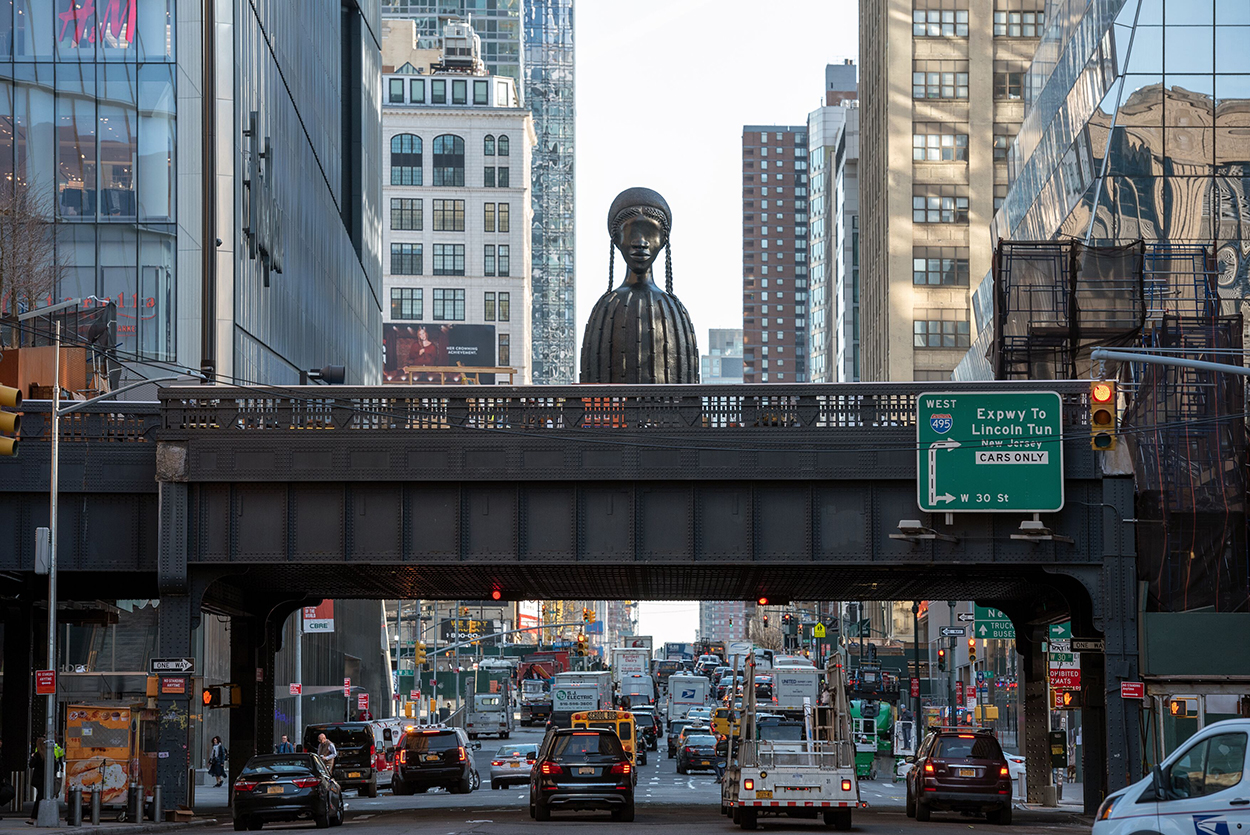 A monumental iron sculpture of a woman with breads and gourd-shaped body is perched on an iron bridge in Manhattan. The city is bustling underneath.