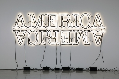 Two neon signs reading America (the bottom one is upside down), installed with the bulbs facing the wall so they create a halo of light around the black lettering