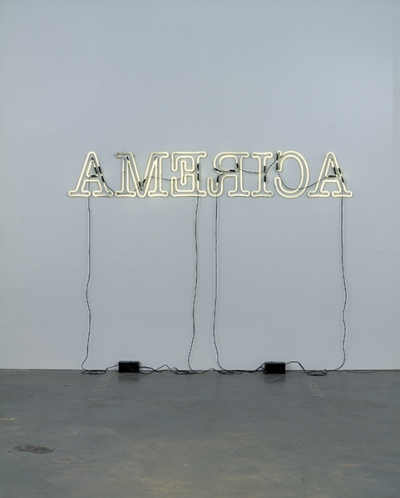 A neon sign spelling America but all the letters are written backwards