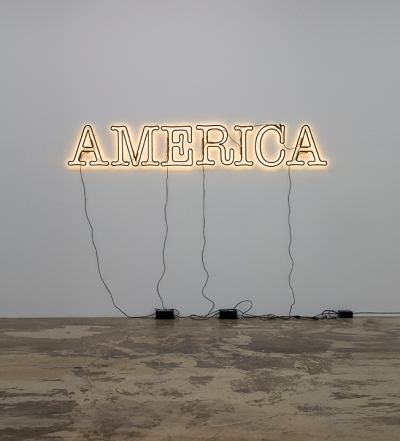 A neon sign reading America hangs on a white wall