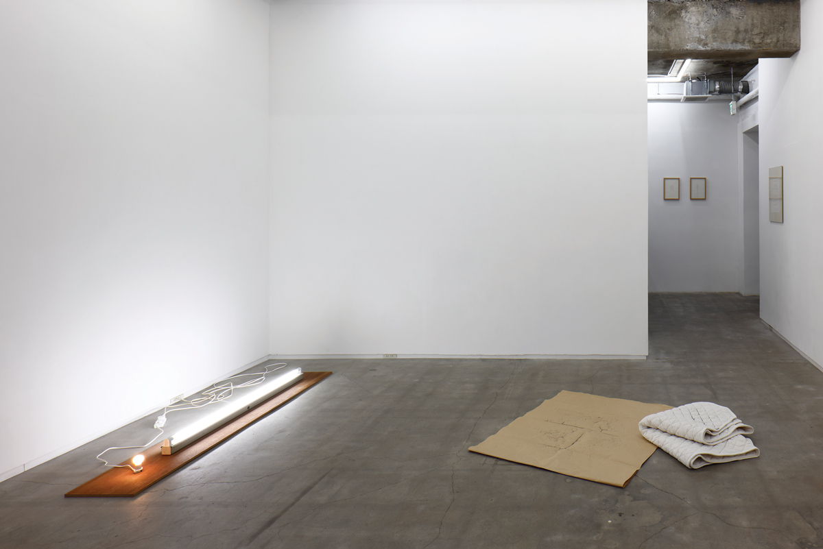 Installation view of a white-cube gallery with two floor installations: at left, a neon tubular light, and, at right, a white blanket on a cardboard piece.