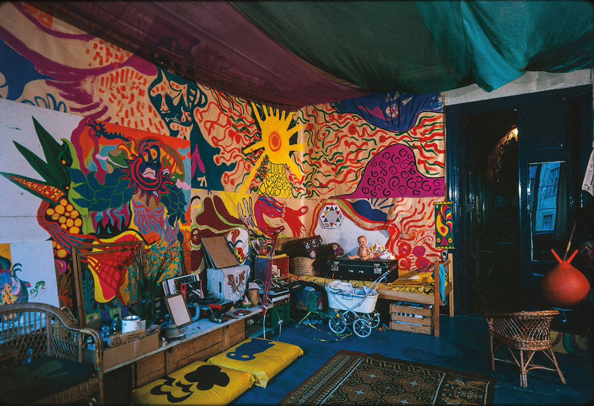 View of a room with various multicolored textiles hanging on the wall and various other objects.