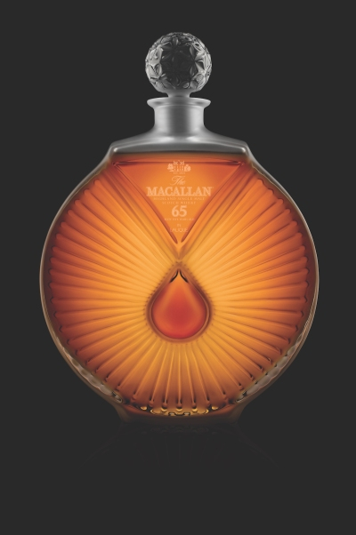 An elegantly shaped circular bottle of whiskey with what appears to be a red teardrop shape at its center.