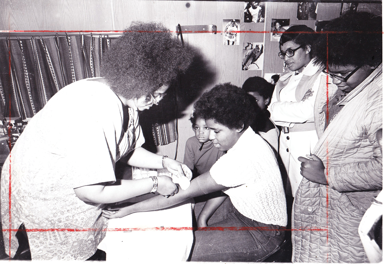 Archival grayscale photo showing a handful of Black people of various ages in a room with wood-paneled walls. They are wearing 70s clothes, and one child is receiving a blood test.