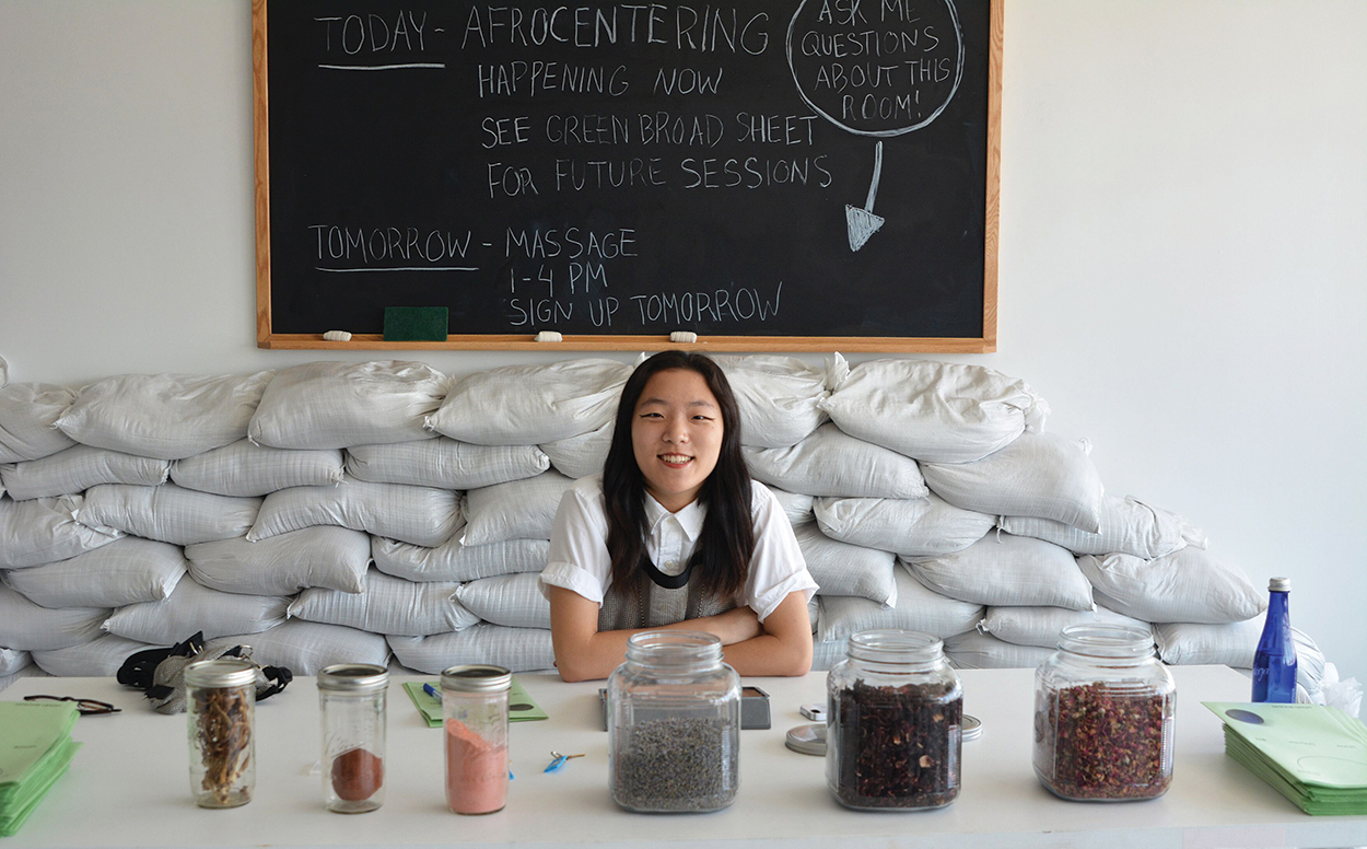An East Asian person with long hair poses behind several jars of herbs and in front of a chalkboard. The person appeares to be managing a desk of some sort.