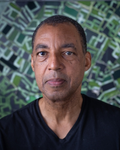 A portrait of a Black man, who is wearing a black v-neck shirt. In the background is one of his abstract black-and-green paintings.