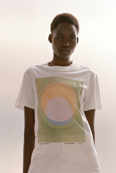 A Black woman wearing a long white T-shirt featuring an abstraction on it.