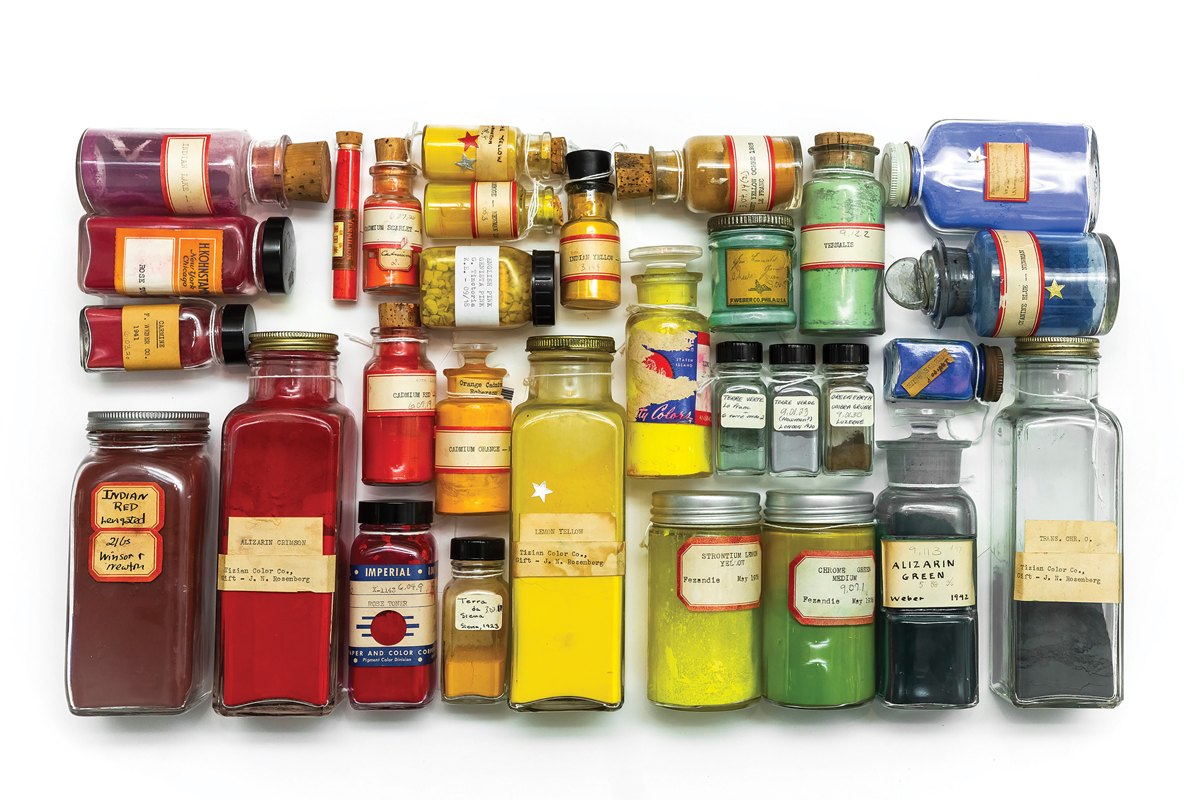 Above view of variously sized glass bottles containing different paint pigments.