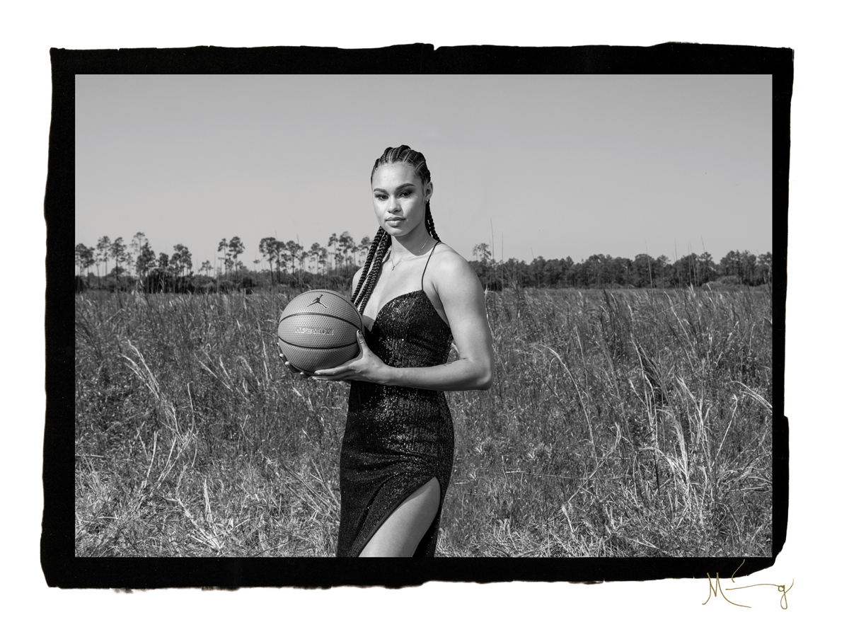 A black-and-white photograph of a Black woman wearing an elegant black dress and holding a basketball in a field.