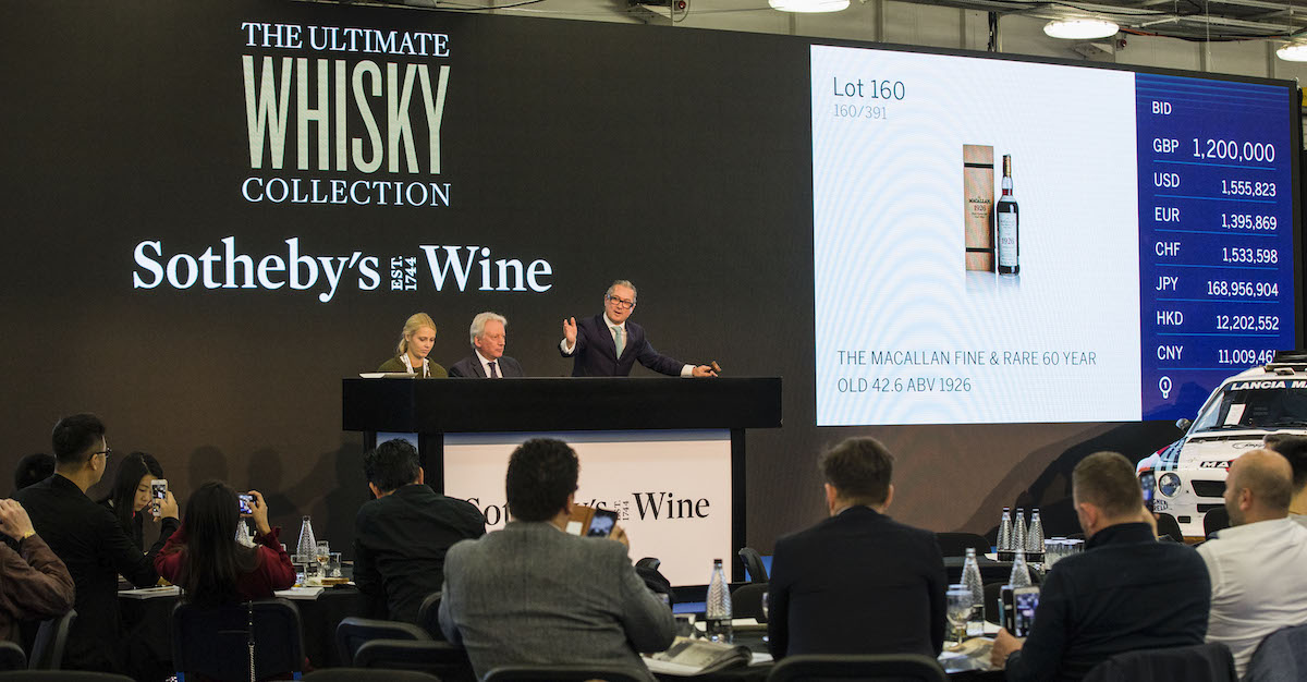 An auctioneer at a platform holds a gavel and stands beside a screen showing an image of a bottle of whiskey. A crowd watches before him.