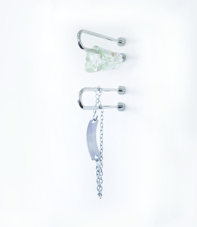 Two chrome grab bars are installed on a wall. One is wrapped in a lumpy glass tube, while an oversized metal medical ID bracelet dangles off the other.