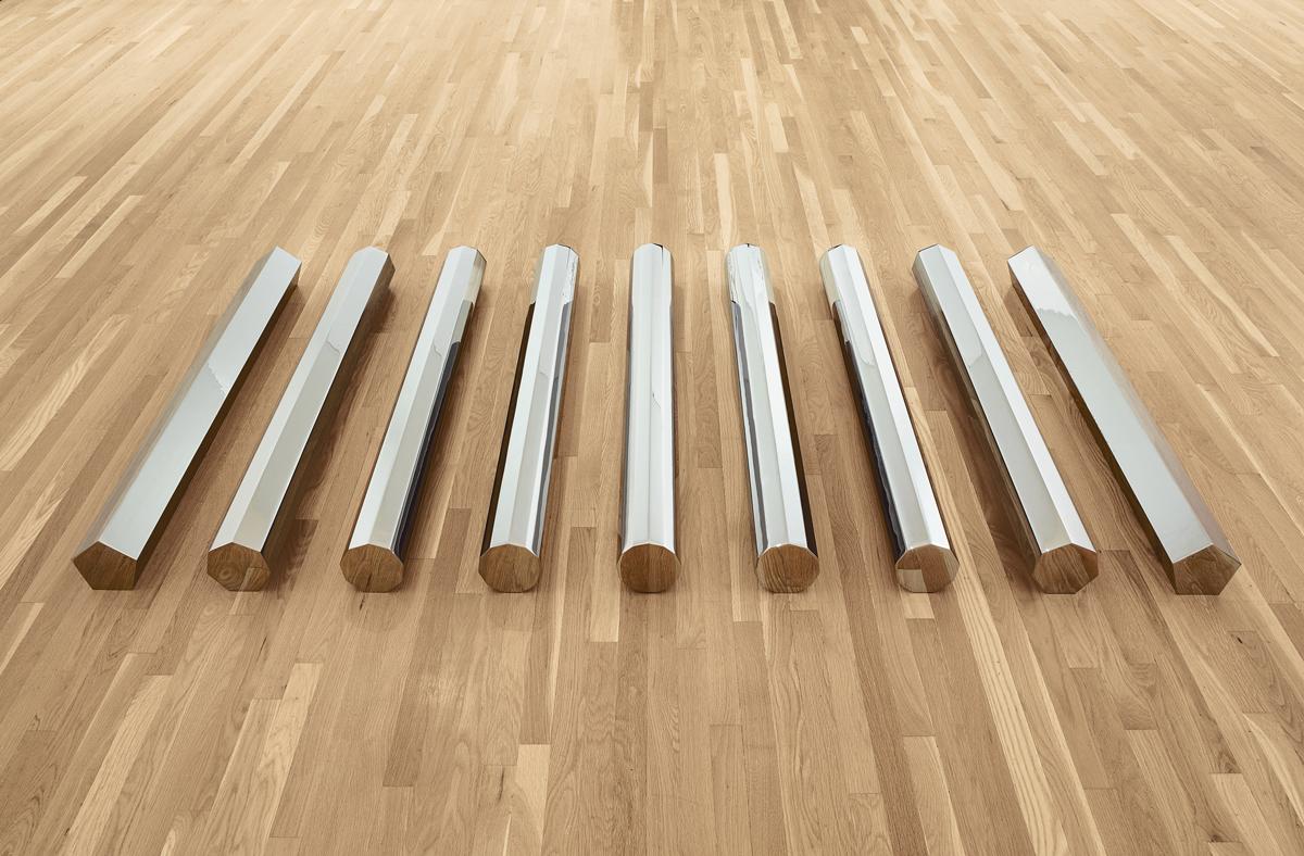 A floor installation of 9 circular metal rods.