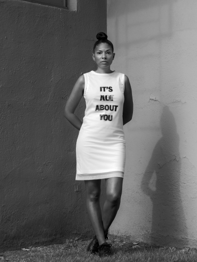 A Black woman wearing a white dress that has on it black text reading 'IT'S ALL ABOUT YOU.'