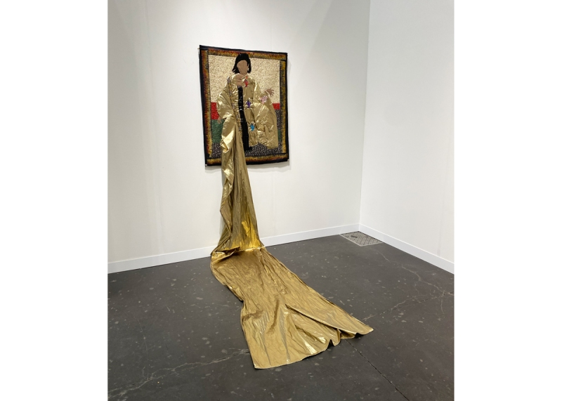 A mixed-media wall work with gold lame train cascading to the floor.