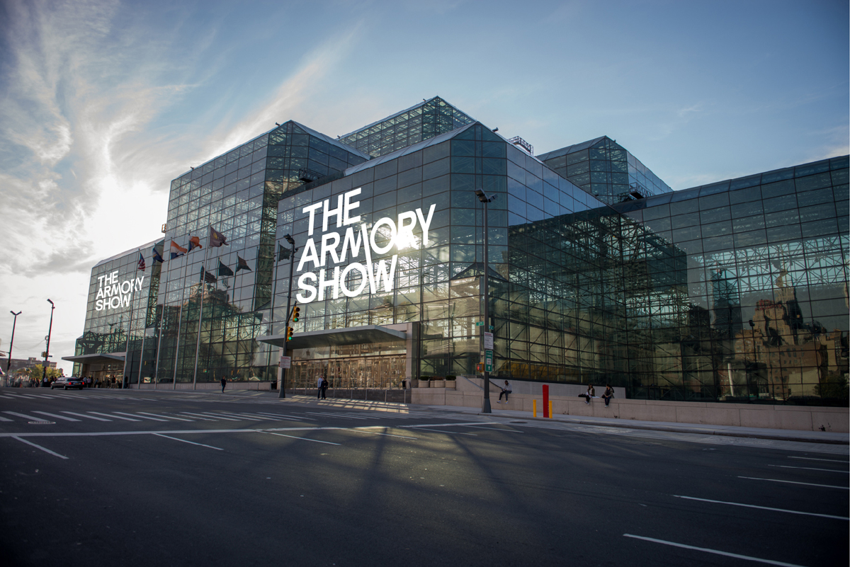 An exterior shot of the all-glass Javits Center, with 'The Armory Show' on its windows.