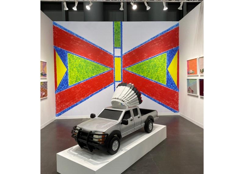 A papier-mâché pick-up truck with a honor bonnet installed in an art fair booth.