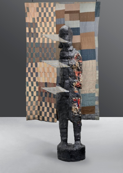 A dark, mysterious sculptural figure with three floating planes protruding stands before a suspended multi-block quilt in subdued hues.