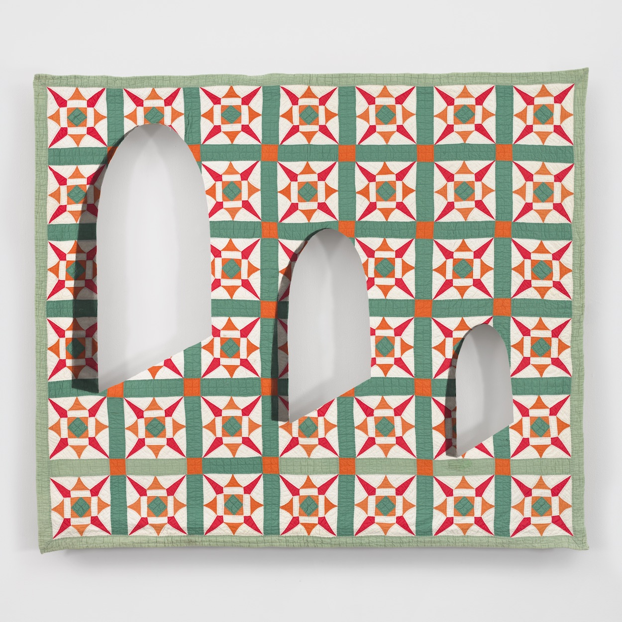 Three spade-like forms, in descending sizes, are juxtaposed in a horizontal row against a quilt with a grid of green, white, and red snowflake patterns.