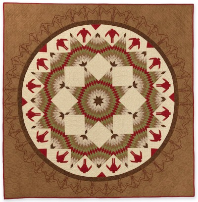 A square brown and tan quilt with concentric rings of symbols and geometric forms at center.