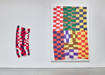 Two quilts of bright multi-colored rectangles, one small and crooked, one large and foursquare, hand side by side on a gallery wall.